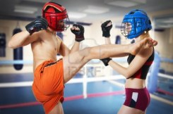 8278290-couple-workout-on-ring-man-and-woman-fighters-in-sports-helmets-guy-kicking-girl-in-head-by-leg-and-
